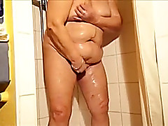 Granny adjacent to the shower rubs her moist love tunnel and fingers levelly