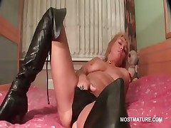 Mature blonde alms-man rubs her muddied pussy in bed