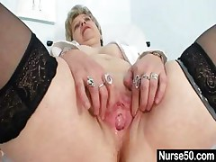 Busty granny in uniform stretching the brush grey pussy