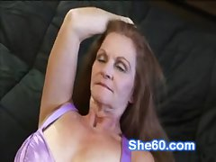 Horny redhead granny fucks her shaved pussy in a dildo
