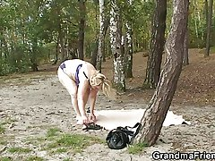Granny rides and sucks on tap same time outdoors