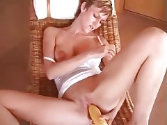 Pretty milf, short haired, rubs her pussy with a corn cob.